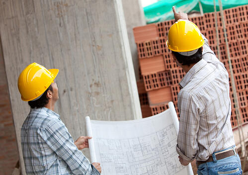 Engineers working and holding a model in a construction