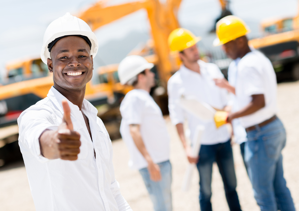 Happy engineer with thumbs up at a construction site