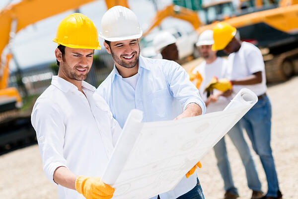 Team of architects at a building site looking at blueprints